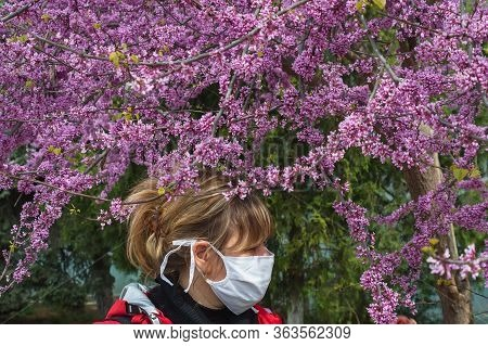 Young Red Haired Girl, In A Red Jacket In A Medical Mask Stands Near A Blossoming Lilac Sakura In Th