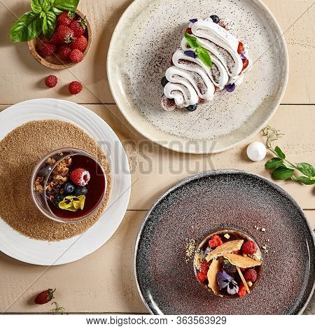 Tasty desserts in ceramic plates top view. Pavlova, Panna Cotta and Tart. Sweet food, sugary bakery, creamy pastry with whipped cream and berries decoration. Served delicious cakes on wooden table