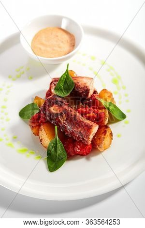 Octopus and baked potato. Served luxury cuisine. Seafood roasted in butter with smoked pepper sauce in white plate isolated. Restaurant high menu food portion. Delicious supper, main course