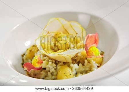 Risotto with pear close up. Served traditional Italian cuisine. Rice with fruit and gorgonzola cheese. Italian restaurant food portion, main course in white plate. Vegetarian supper