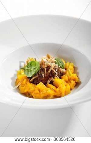 Beef cheek with baked celery root ragout. Served luxury cuisine. Meat with vegetable and parmesan cheese in white plate isolated. Restaurant high menu food portion. Delicious supper, main course