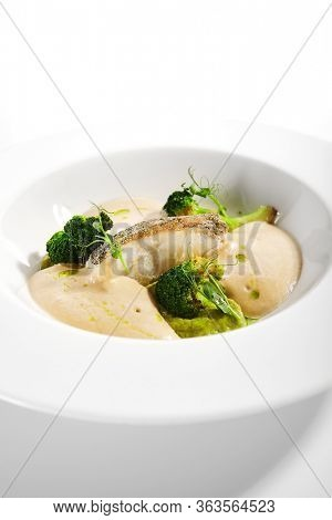 Sea cod fillet close up. Served cuisine. Dish with fish and baked broccoli puree ingredients in white plate isolated. Luxury culinary. Restaurant food portion, delicious supper, main course