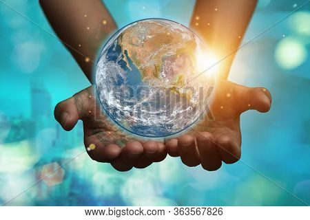 International Day Of Forests And Earth Day Concept: Hands Holding Blue Earth Globe Over And Blurred