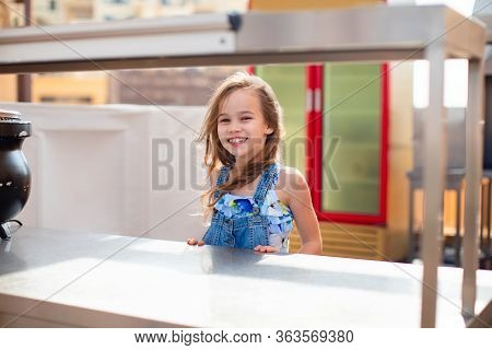 Little Girl Child Standing Behind An Empty Counter, A Serving Table In The Dining Room, Caf Under Th