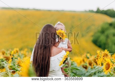 Beautiful Mother Are Hugging With The Daughter In The Field Of Sunflowers. Woman With Long Hair And
