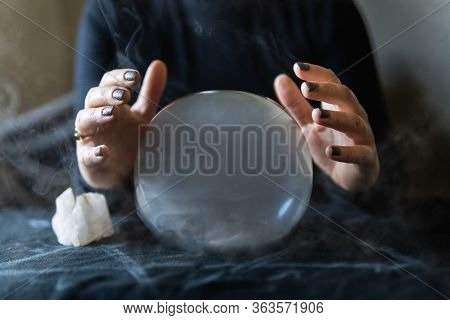 Fortune Teller Holding Hands Above Magic Crystal Ball With Smoke Around