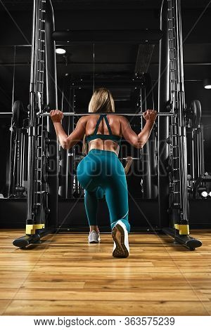 Sporty Sexy Girl Trains Legs Doing Exercises With Heavy Weight On A Barbell. Achieving Goals Overcom
