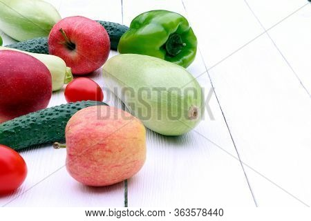 Vegetables And Fruits. Tomatoes And Cucumbers, Apples And Squash On A Wooden Table. Green Pepper. Or