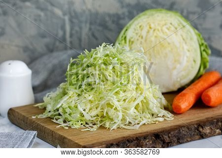 Fresh Young Shredded Cabbage On A Wooden Board And Half A Cabbage And Carrots Nearby