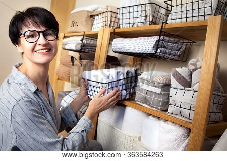 A Woman Is Doing Spring Cleaning. Folds Bedding, Blankets, Towels And Duvet Covers In A Closet. The