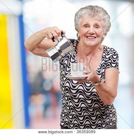 portrait of a vitality senior woman serving a tea cup indoor