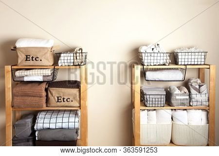 Bed Sheets, Duvet Covers And Towels Are Folded Vertically. Metal And Fabric Black Baskets. The Conce