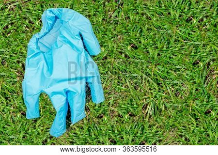 The Blue Used Medical Glove Lies On The Left On The Green Grass. Concept Of Protecting A Person From