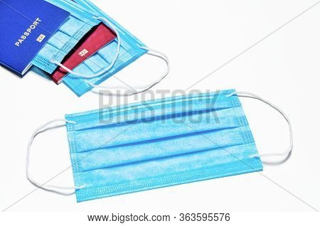 Blue Medical Facial Mask Lies On A White Background. In The Background Are Two Foreign Passports Of