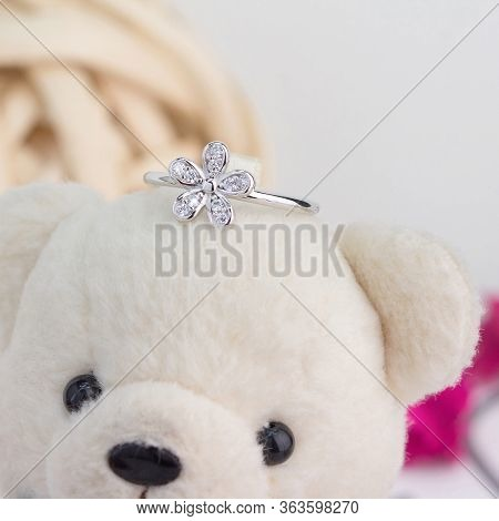 Cute Silver Ring In The Flower Shape Decorated With Diamonds Display On Toy Bear