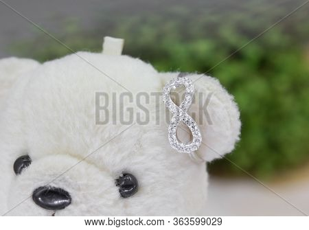 Beautiful Infinity Shape Silver Ring Decorated With Diamonds Display On Toy Bear