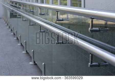 Chrome Railing Outside The Building. A Line Of Tubular Railings On Top Of A Glass Railing. Selective