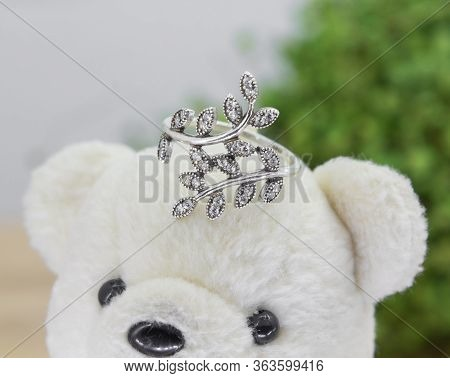 Silver Ring In The Shape Of Olive Leaves Decorated With Diamonds Display On Toy Bear