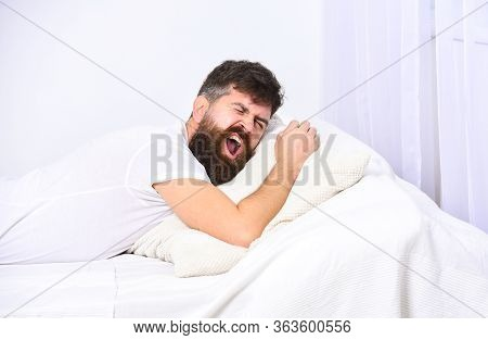 Man In Shirt Laying On Bed, White Wall On Background. Nap And Siesta Concept. Guy On Sleepy Tired Fa