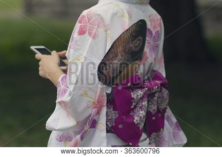 Girl In A Beautiful Kimono With A Smartphone. Japanese Culture