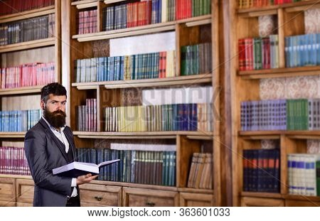 Bookstore And Literature Concept. Brutal Man Holds Book In Bookstore.