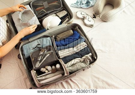 Open Grey Suitcase With Different Clothes Packed For Journey At Home. Nordic Style Minimalism. Woman