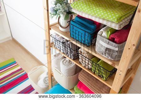 Bed Sheets, Duvet Covers And Towels Are Folded Vertically. Metal And Fabric Black Baskets. Bedclothe