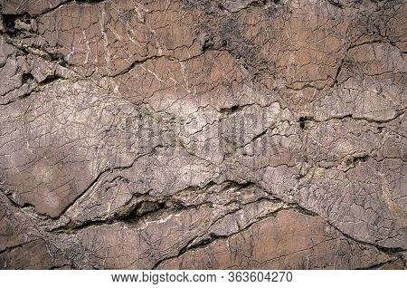 Old Cracked Fracured Stone Background Texture. Rough Weathered Split Stone Surface With Erosion Crac