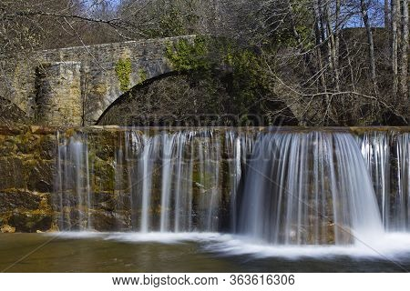 Sarria, Araba/basque Country; Mar. 18, 2017. Dam And An Old Bridge Over The Bayas River As It Passes