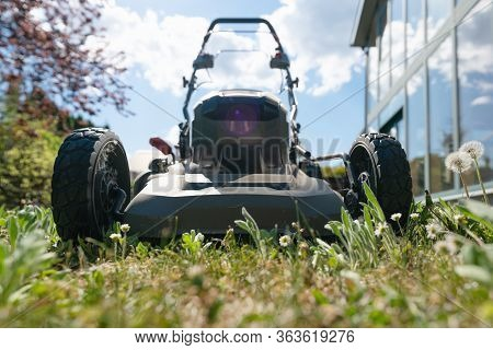 Front Low Angle Shot Of Blurred High Grass With Mowing Machine On Sunny Day In A Garden