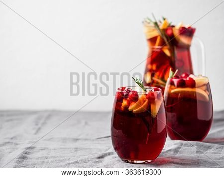 Winter Sangria On Tabletop With Gray Linen Tablecloth. Jugful Of Sangria And Glasses With With Fruit