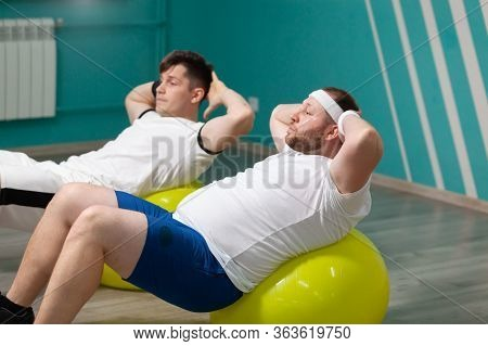 Tired Fat Man Is Lying On A Fitness Ball Training During Group Fitness Classes. Overweight