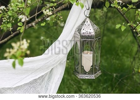 Ornamental Silver Moroccan Lantern Handing On Blooming Tree. Green Blurred Background With White Vei