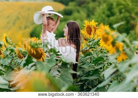 Happy Mother With The Daughter In The Field With Sunflowers. Mom And Baby Girl Having Fun Outdoors.