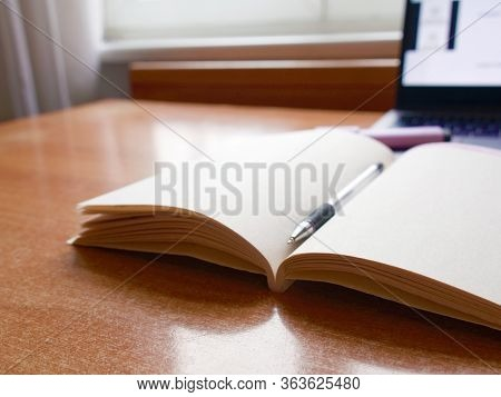 Laptop And Open Notebook On Wooden Table, Window Background. Concept Remote Study And Work At Home,