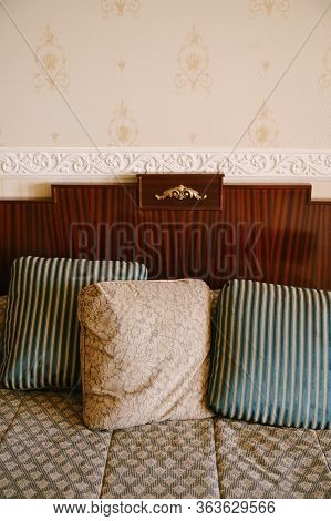Pillows On The Bed. A Pillow With A Pattern And Two Pillows With Stripes Lie On An Old Wooden Bed