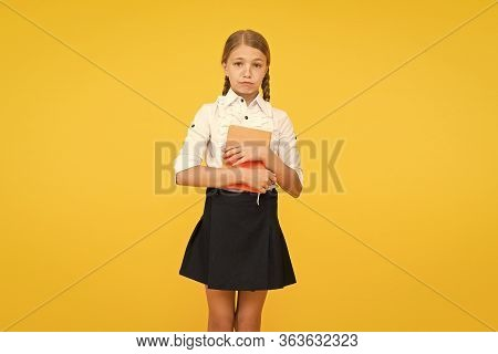 What A Sad News. Sad Schoolgirl Holding Book On Yellow Background. Adorable Little Child In School U
