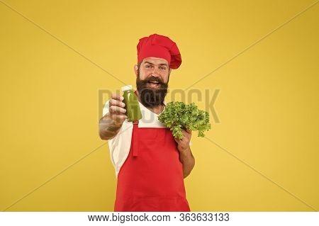 Detox Program. Fresh Juice. Squeezing Smoothie. Man Bearded Chef Hold Lettuce And Smoothie Bottle Ye