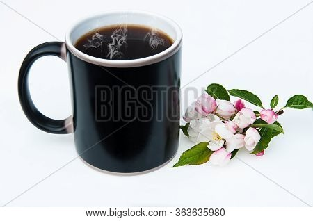Black Coffee Cup With Cherry Blossoms Still Life.  This Coffee Mug Has Steaming Hot Black Coffee Wit