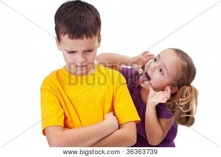 Young girl mocking angry boy - isolated