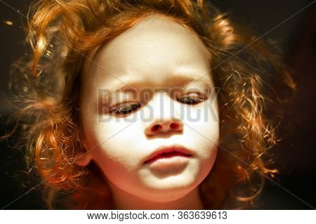 Red-haired Little Girl With A Doll Face With Hard Sun Light And Luminous Hair. Cute Fairy Baby.