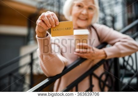 Happy Elderly Female With Credit Card Outdoors Stock Photo