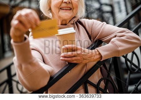Smiling Grandma With Credit Card Outdoors Stock Photo