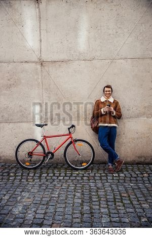 Mirthful Cyclist Relaxing By The Wall Outdoors And Smiling