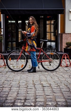 Mirthful Lady In Front Of The Hotel Entrance With Bike And Gadget