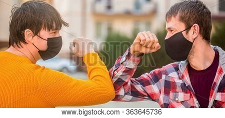 Elbow Bump. Friends Medical Mask. People Wear Face Mask Outside. Friends Bump Elbows Outdoors. Coron