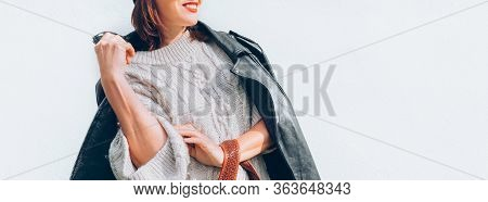Smiling Female Dressed Fashion Style Warm Knitted Sweater With Black Leather Biker Jacket And Beanie