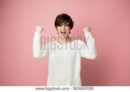 Beautiful young woman happy and excited expressing winning gesture. Successful pretty girl celebrating victory, triumphant, studio shot over pink background