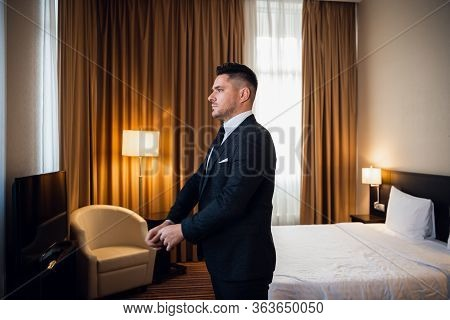 Young Handsome Businessman Adjusting His Jacket, Dressing Up At His Luxury Hotel Suite Preparing For