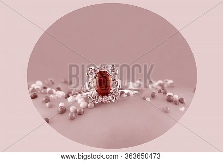 Garnet And Diamond Solitaire Ring Highlighted In A Circle Against A Pink Monotone Background